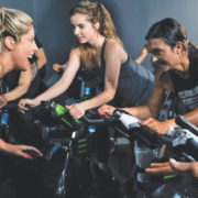 Blonde woman trainer motivating clients during a spin class.