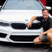Auto shop owner sitting down beside white BMW sedan.