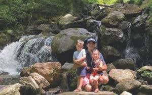 A father with his two young children sitting in front of a waterfall for photo.