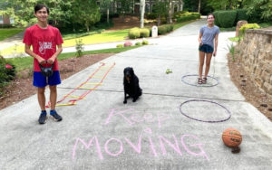 A brother and sister with their black lab doing obstacle course in their driveway.