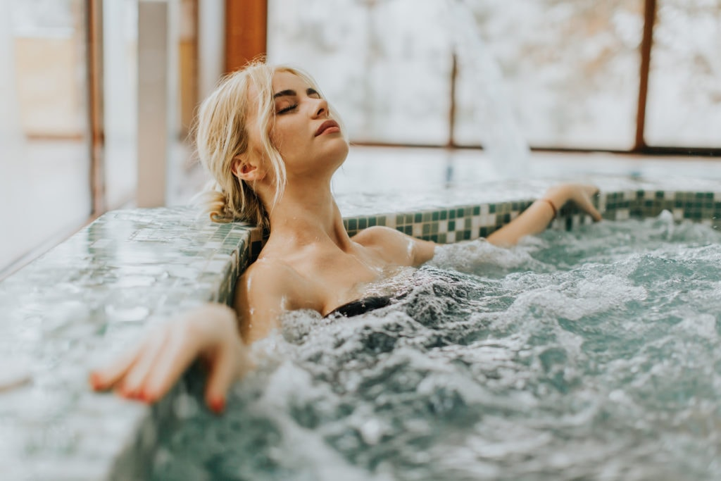 Woman lounging in a hot tub - stock