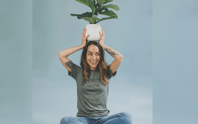 Sophia with a plant on her head in front of a blue background