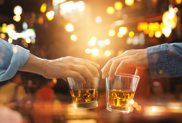 Two men cheersing with whiskey