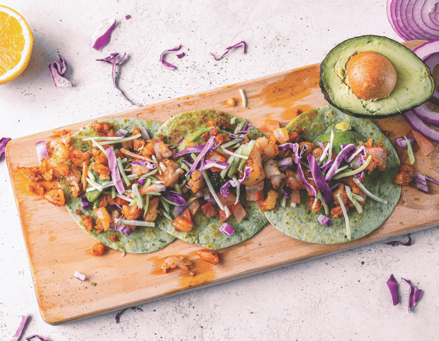 Three tacos arranged on a wooden board