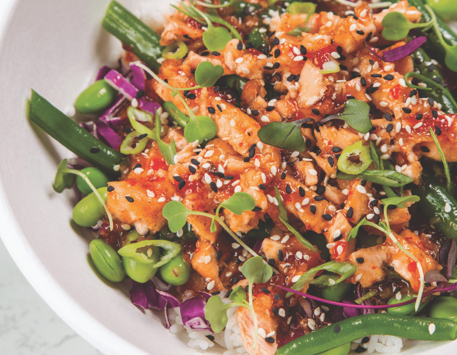 sweet and spicy salmon bowl with orange sauce on top