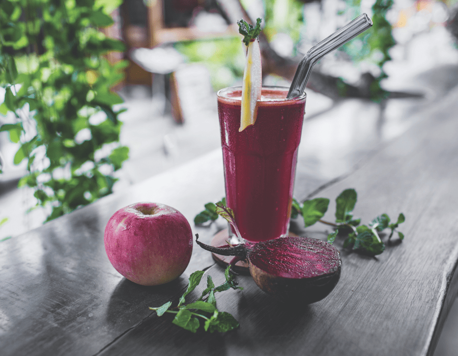 Purple juice in glass on wooden bar