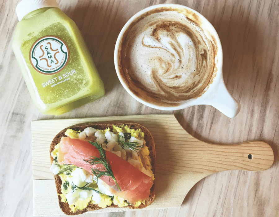 Fresh juice with coffee and order of salmon toast on board and wooden table