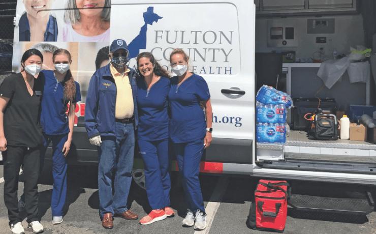 Tuxedo Pharmacy employees in front of vaccination van