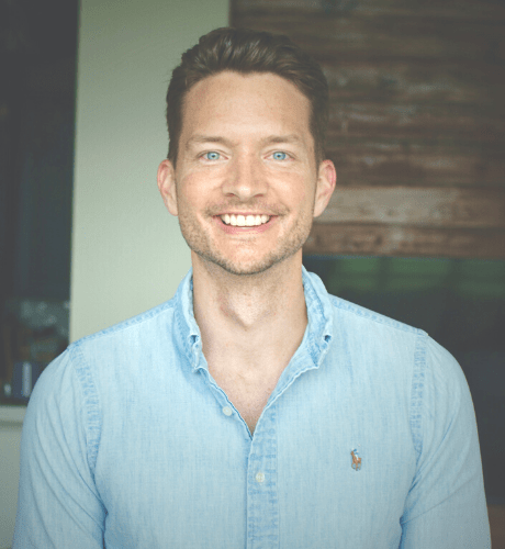 Man in blue shirt with blue eyes smiling at camera