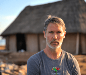 Kerry Stumpe in front of thatch roof