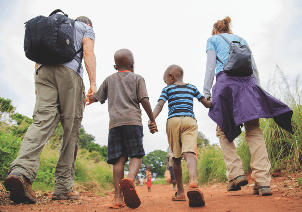 Man and women walking holding hands with two ugandan children