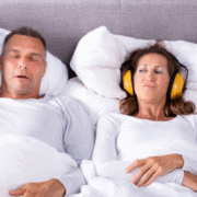 Woman looking angrily at her partner snoring